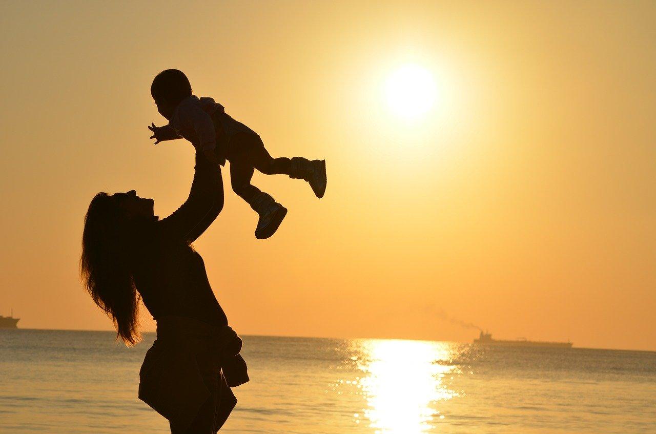 Майка с малко бебе на залез слънце